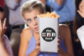 Terrified young multiethnic friends sitting in cinema, watching horror movie and covering faces in fear. Caucasian girl sitting between Asian friends with popcorn